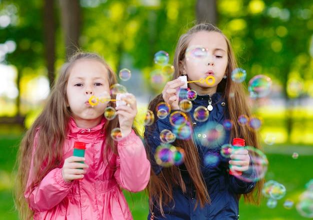 Dziewczyny bawią się bańkami mydlanymi.