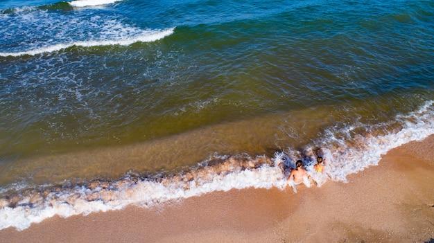 Dziewczyny bawią się na brzegu morza i widoku z góry drona