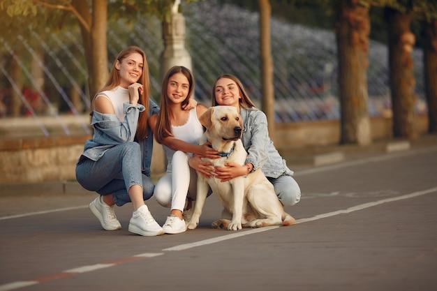Dziewczyny chodzą w mieście wiosny z uroczym psem