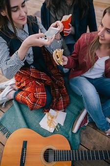 Dziewczyny co zdjęcie fast foodu przez smartfona. zbliżenie na spotkanie z przyjaciółmi, odpoczynek na świeżym powietrzu i komunikacja, wspólne spędzanie czasu, wesoła atmosfera przy muzyce