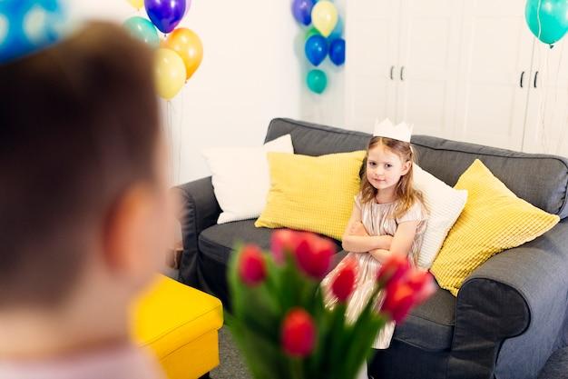 Dziewczyny czekanie kwitnie na kanapie