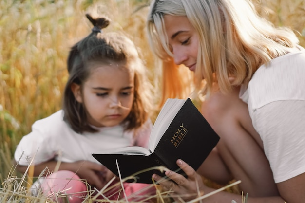 Dziewczyny czytają pismo święte w polu pszenicy. studiujcie razem biblię.