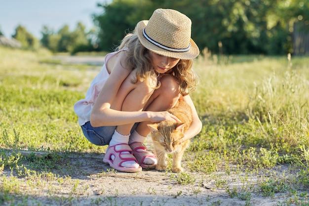 Dziewczyny dziecko w kapeluszu na wiejskiej drodze bawić się z czerwonym kotem, pogodny letniego dnia wieśniaka styl
