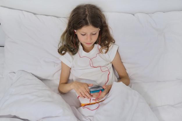 Dziewczyny dziecko z telefonem komórkowym w hełmofonach, siedzi w domowym białym łóżku