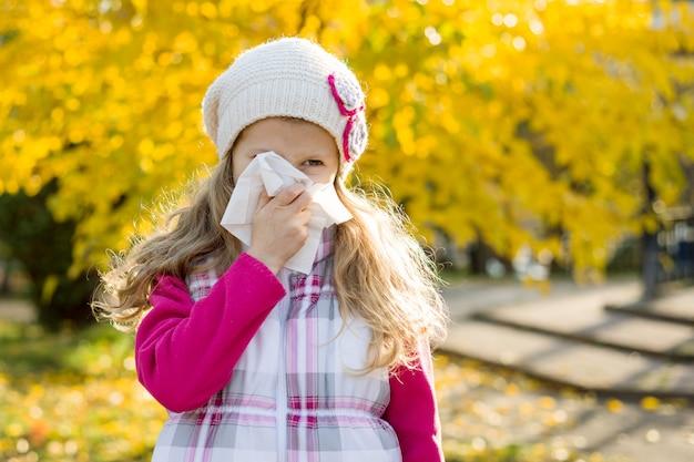 Dziewczyny dziecko z zimnym nieżytem nosa na jesieni tle