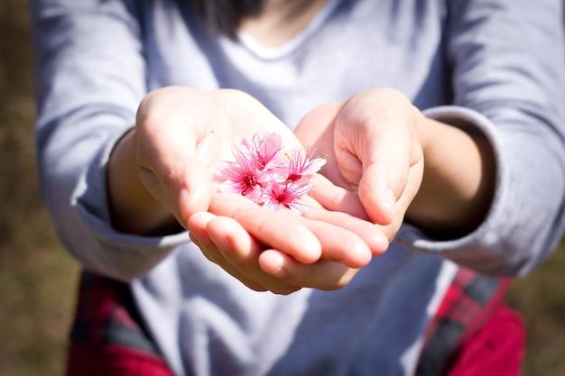 Dziewczyny dzielą się kwiatami na swoich rękach.