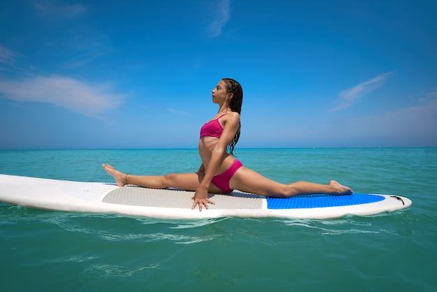 Dziewczyny gimnastyka na paddle surfuje deskę sup