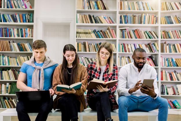 Dziewczyny i chłopaki, zapraszają studentów studiujących razem w bibliotece, trzymających tradycyjne książki i cyfrowe tablety. nauka z papierowymi książkami i gadżetami e-learningowymi.