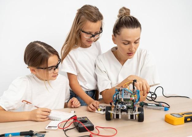 Dziewczyny i nauczycielka wspólnie przeprowadzają eksperymenty naukowe