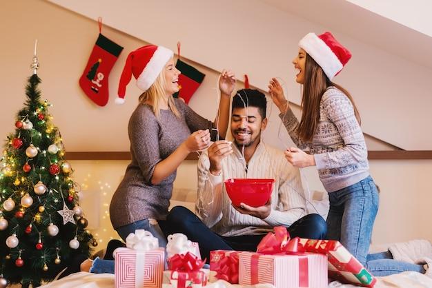 Dziewczyny, które zapalają bożonarodzeniowe lampki swoim znajomym, bawią się, gdy on je popcorn.