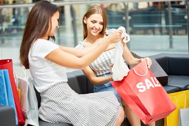 Dziewczyny kupujące ubrania w centrum handlowym