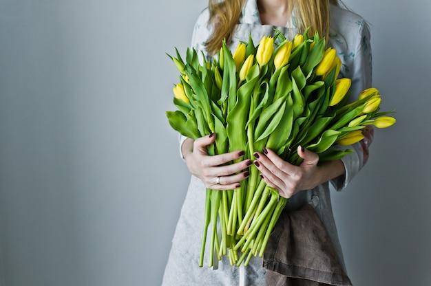 Dziewczyny kwiaciarnia trzyma wiązkę żółci tulipany. florystyczny.