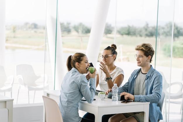 Dziewczyny łasowania jabłko przy stołem z innymi ludźmi