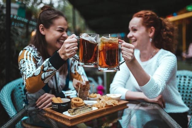 Dziewczyny latem bawią się i piją piwo w ulicznej kawiarni.