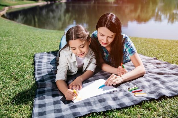Dziewczyny leżą na kocu tego pięknego słonecznego dnia na trawie. do rysowania używają kolorów niebieskiego i żółtego. dziewczyny wyglądają na zainteresowanych.
