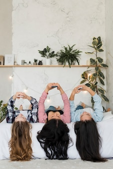 Dziewczyny leżące za pomocą telefonów nad głowami