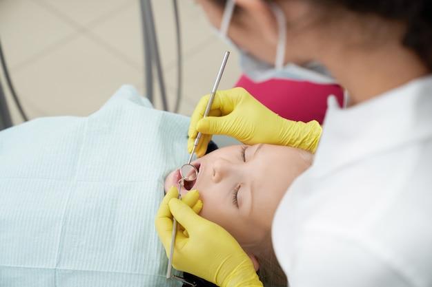 Dziewczyny lying on the beach na stomatologicznym krześle z otwartym usta w klinice