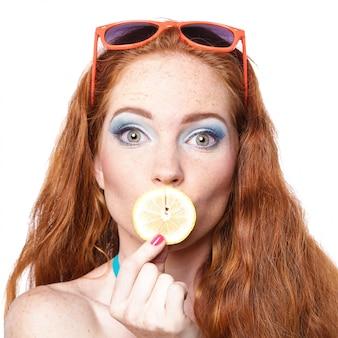 Dziewczyny mienia cytryna na bielu. odosobniony