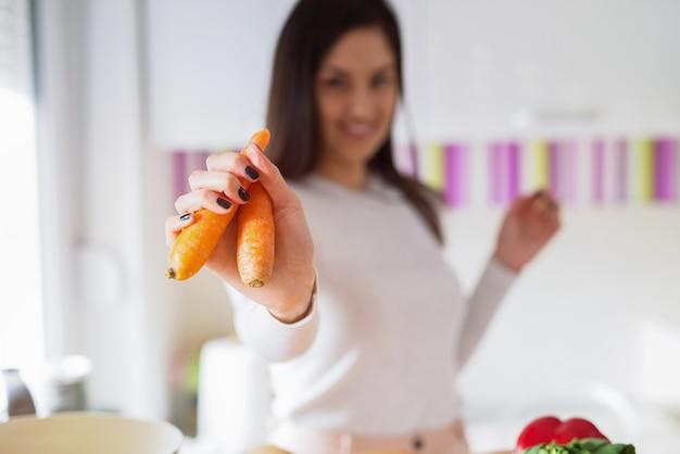 Dziewczyny mienia marchewki w ona ręka podczas gdy stojący w jaskrawej kuchni.