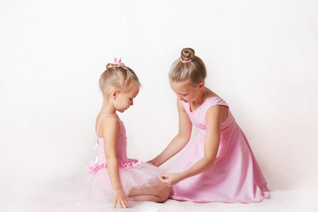 Dziewczyny młode baleriny w różowych sukienkach na jasnym tle