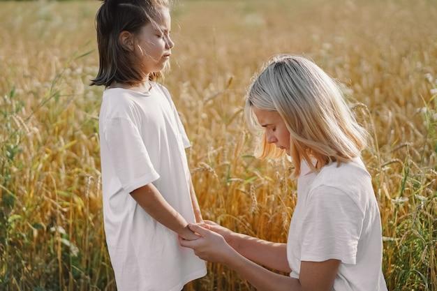 Dziewczyny, modląc się i trzymając się za ręce w polu pszenicy. módlcie się o wzajemne wsparcie boga.