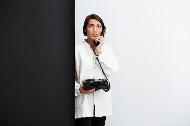 Dziewczyny mówienie na starym telefonie nad czarny i biały ścianą