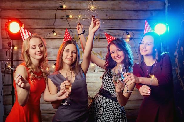 Dziewczyny na przyjęcie urodzinowe w czapkach na głowach iz zimnymi ogniami w dłoniach.