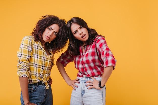 Dziewczyny o brązowych oczach patrzą z oburzeniem i potępieniem. migawka niezadowolonych przyjaciół w podobnych koszulach.