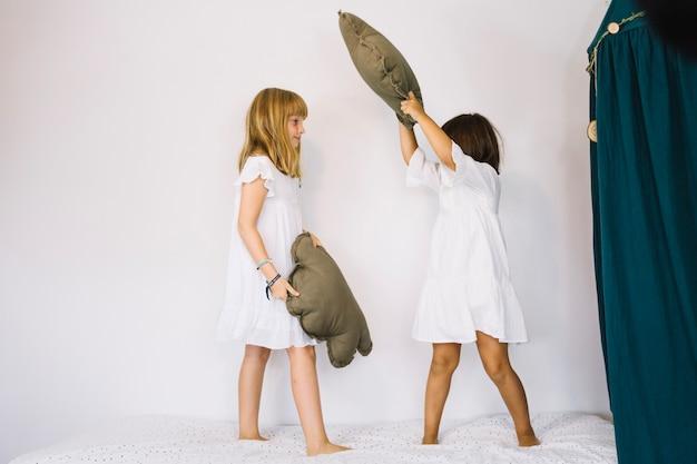 Dziewczyny o poduszkach walczą w łóżku