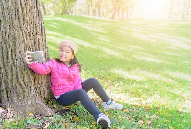 Dziewczyny obsiadanie i bierze selfie na zielonej trawie