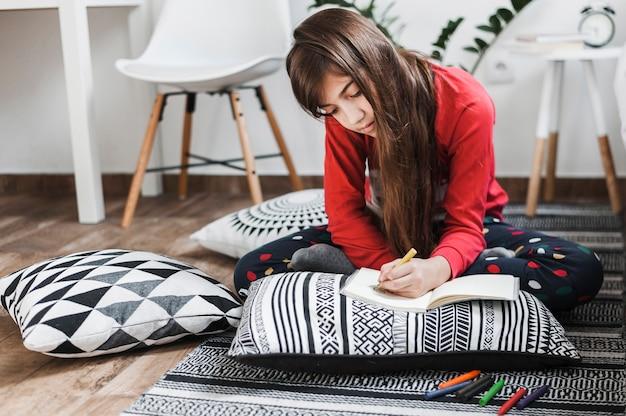 Dziewczyny obsiadanie na dywanika rysunku z kolorowymi kredkami na notatniku