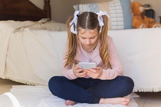 Dziewczyny obsiadanie na poduszce patrzeje telefon komórkowego w sypialni