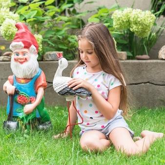 Dziewczyny obsiadanie na zielonej trawie bawić się z statuą
