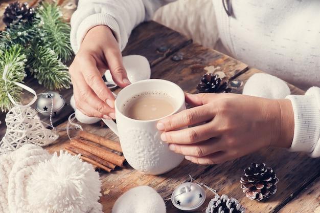 Dziewczyny obsiadanie przy jej biurkiem pije kawę