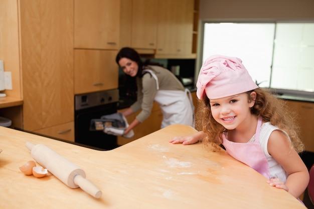 Dziewczyny obsiadanie w kuchni podczas gdy jej matka stawia ciastka w piekarnika