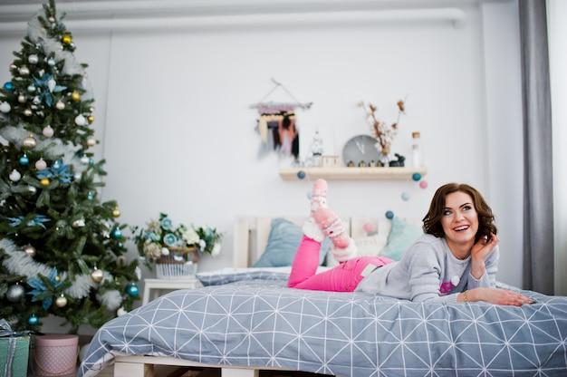 Dziewczyny odzież na zima swetra łóżku w pokoju z choinką.