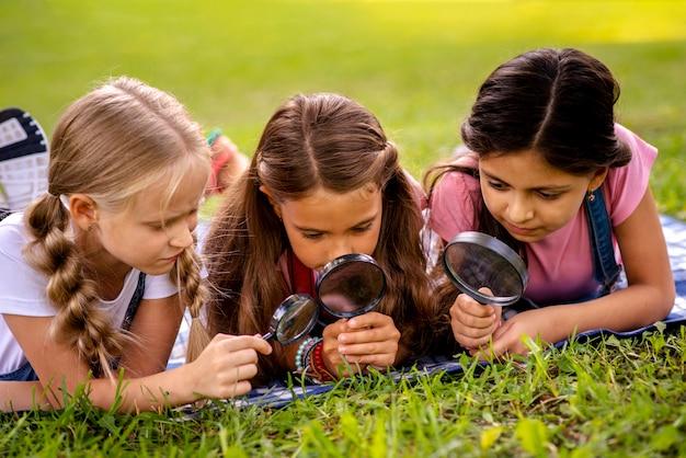 Dziewczyny patrzą na trawę przez szkło powiększające