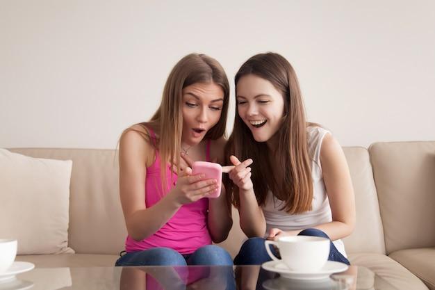 Dziewczyny patrzeje na śmiesznych fotografiach na telefonie komórkowym