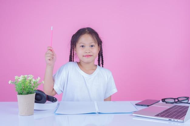 Dziewczyny piszą książki na różowym tle.