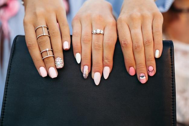 Dziewczyny pokazujące jej stylowy manicure, trzymające trzy palce na czarnej torebce.