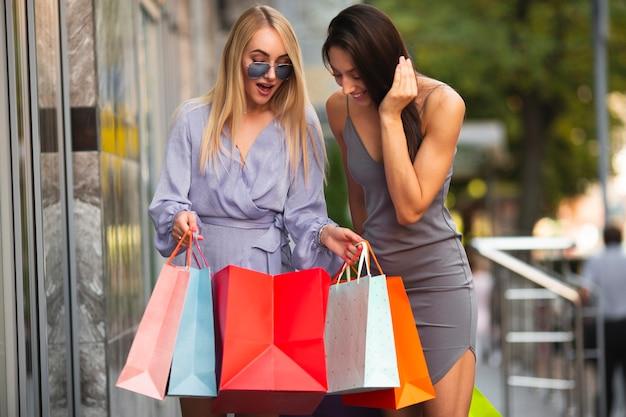 Dziewczyny pokazujące sobie nawzajem to, co kupili