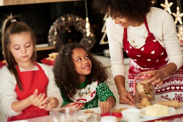 Dziewczyny pomagają mamie robić ciasteczka na boże narodzenie