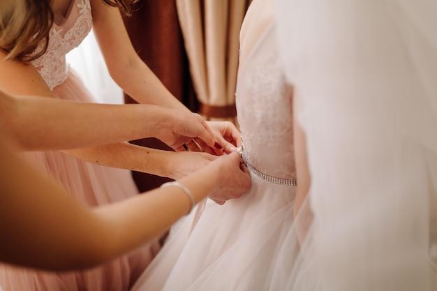 Dziewczyny pomagają pannie młodej założyć sukienkę