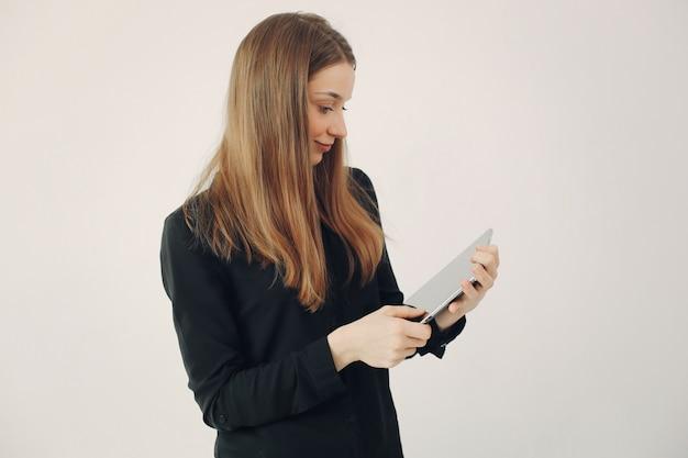 Dziewczyny pozycja na białej ścianie z laptopem