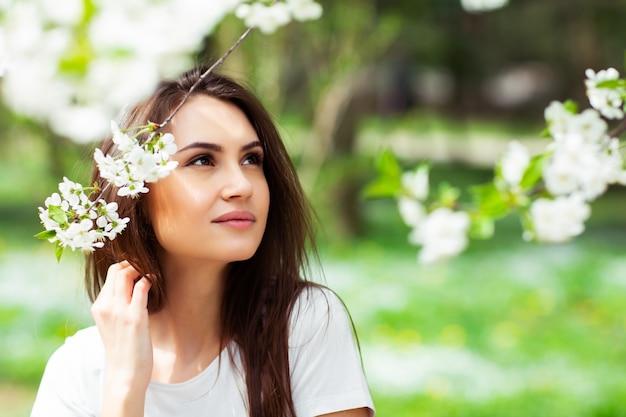 Dziewczyny pozycja pod kwitnąć jabłoni w naturalnym parku. koncepcja mody. elegancka młoda dama w dżinsach, ciesząc się kwitnącym ogrodem w słoneczny wiosenny dzień. naturalny makijaż piękno. poziomy