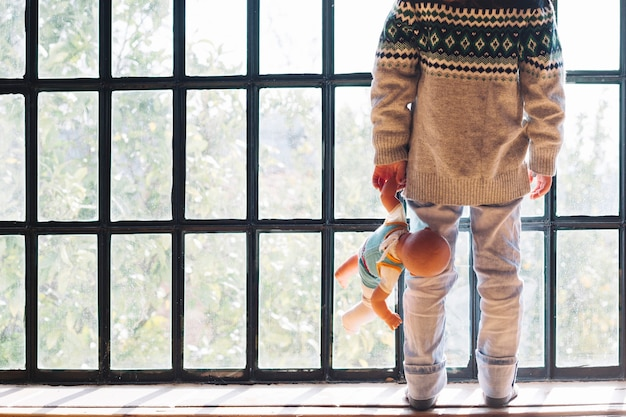 Dziewczyny pozycja przed okno z lalą