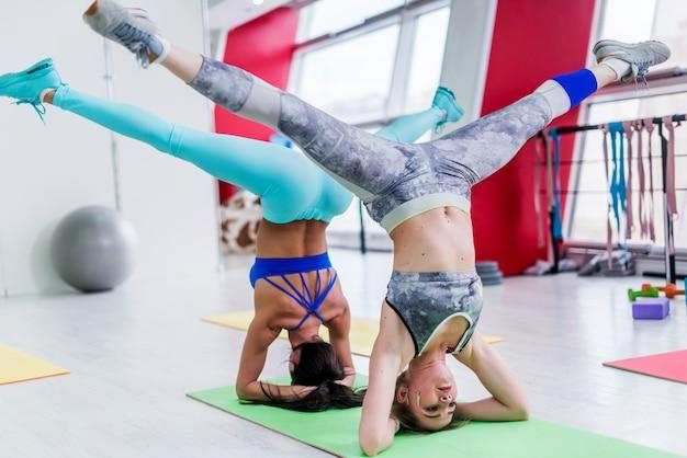 Dziewczyny pracujące razem, wykonujące szerokie nogi na głowie, zaawansowana joga w nowoczesnym klubie fitness