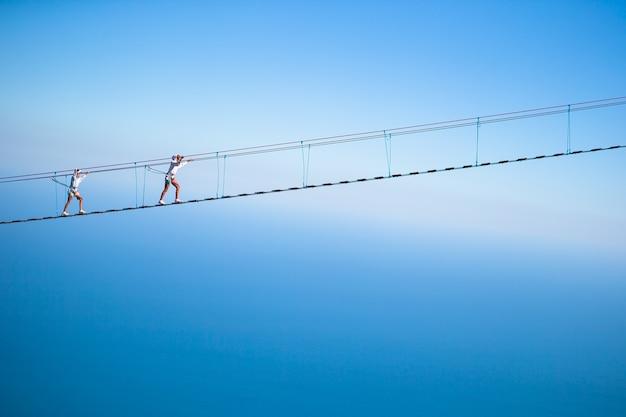 Dziewczyny przekraczające przepaść na moście linowym.