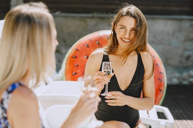 Dziewczyny przy basenie. przyjaciele w stylowych kostiumach kąpielowych. panie na wakacjach.