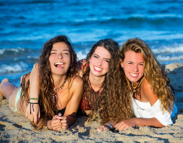 Dziewczyny przyjaciele ma zabawy szczęśliwego lying on the beach na plaży